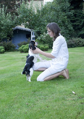 Girl playing with pet dog in backyard