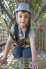 Boy climbing through net in playground tunnel