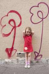 Little girl leaning against wall with flower graffiti  portrait