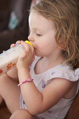 Little girl drinking milk from bottle  side view