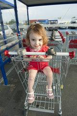 Little girl sitting in shopping cart