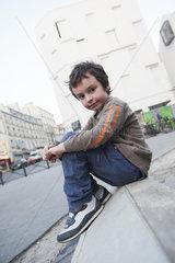 Boy sitting on curb  portrait