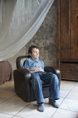 Boy napping in armchair