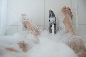 Man soaking in bubble bath  low section