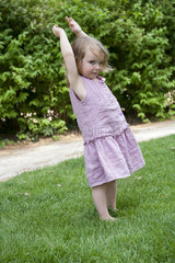 Little girl standing outdoors with arms raised
