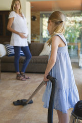 Little girl vacuuming  pregnant mother in background