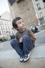 Boy sitting on curb  looking up