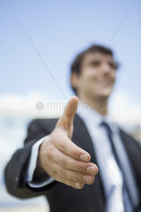 Businessman extending hand for handshake  low angle view