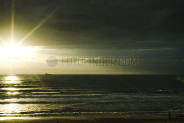 Sunset over the Atlantic Ocean  ship on the horizon  Ondres France