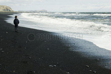 Boy walking on the beach watching the horizon  iceland