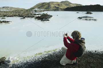 Boy photographing around the Blue Lagoon  Iceland