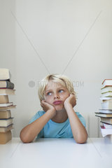 Boy sitting between tall stacks of books  bored expression on face