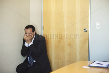 Businessman crouching in corner with terrified expression