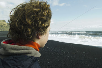 Boy looking horizon facing the sea  iceland