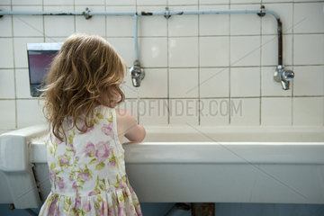 Little girl washing hands in bathroom  rear view