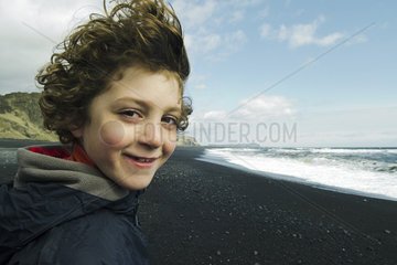 Portrait of a boy smiling on a beach  iceland