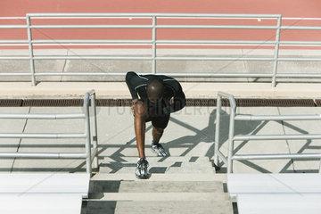 Man stretching legs on bleachers