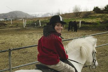 Smiling boy on a Icelandic horse  Iceland