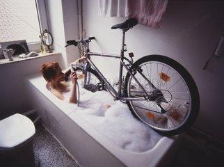 Frau waescht Fahrrad in Badewanne