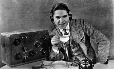 Mann am Radio mit Kopfhoerer und Kaffeetasse