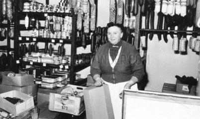 Frau steht hinter Ladentheke