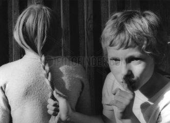 Junge zieht Maedchen an den Haaren