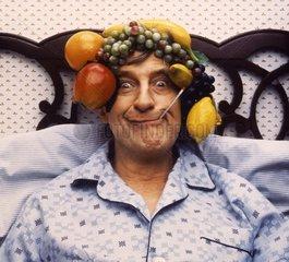 Mann mit Obst auf dem Kopf