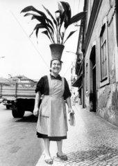 Frau mit Blumentopf auf Kopf