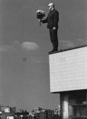 Mann steht mit Blumen auf Dach