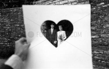 Brautpaar hinter ausgeschnittenem Herz