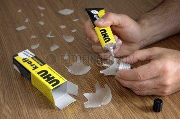 Mann repariert Gluehbirne mit Uhu