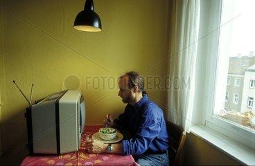 Mann isst vor der Glotze