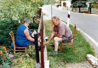 Ehepaar streicht Gartenzaun von unterschiedlichen Seiten