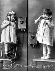 2 Maedchen altes Telefon Stuhl