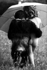 Schimpanse mit nacktem Maedchen unterm Regenschirm