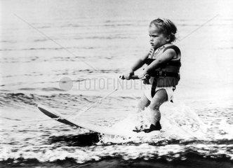 Kleiner Junge faehrt Wasserski