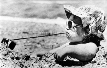 Kind am Strand trinkt mit langem Strohhalm