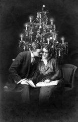 Paar sitzt vor Weihnachtsbaum  1900