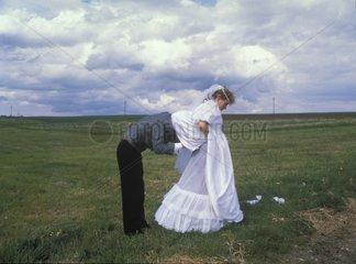 Braeutigam unter Brautkleid