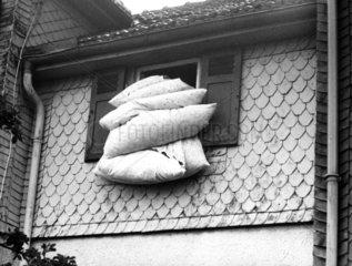 Bettwaesche haengt aus dem Fenster