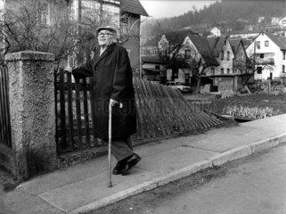 alter Mann lehnt an Zaun