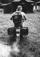 Mann transportiert Bierkaesten mit Moped
