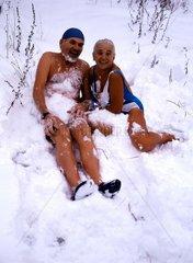 Paar sitzt halbnackt im Schnee