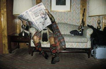 Mann in Schottenrock liest Zeitung