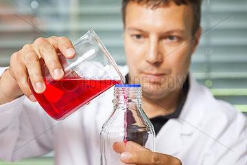 Ein junger Laborant  der mit Chemikalien experimentiert