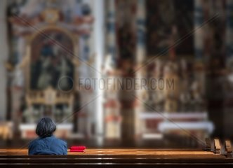 Senior in silence and tranquility within a church