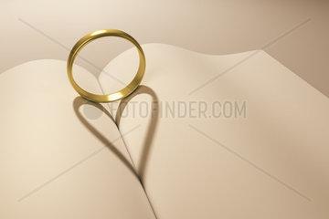 Ein goldener Ring  der einen herzfoermigen Schatten auf ein Buch wirft