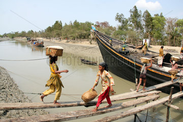 Labourers carry basket of salt