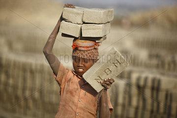 Child worker carrying bricks