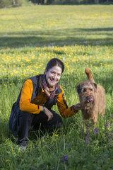 junge frau mit irischem Terrier auf blumenwiese
